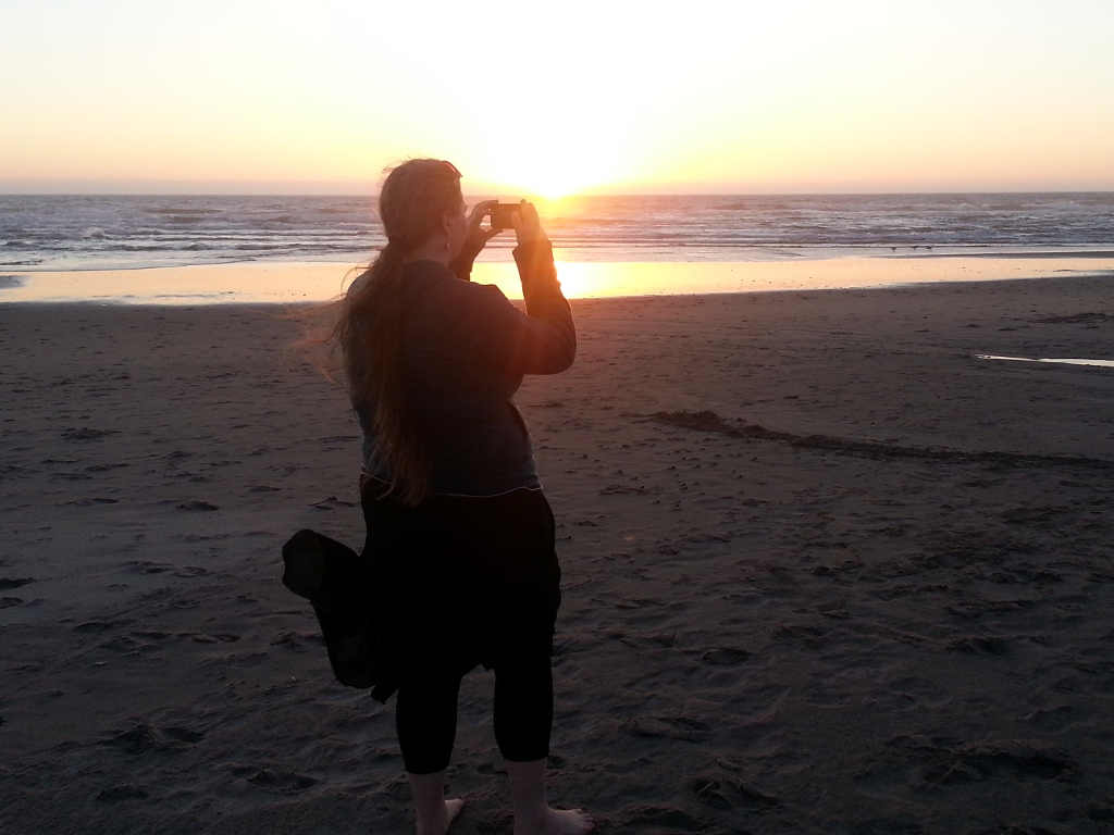 Picture of lovely lady taking a picture of a beach sunset