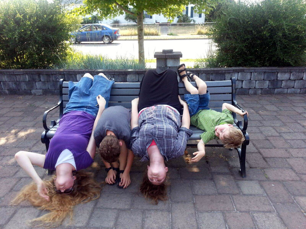 Picture of four kids on a park bench